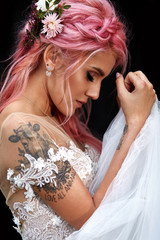 Stunning bride with pink hair and tattoos on her shoulder poses outside
