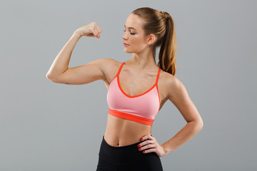 Amazing young sports woman showing biceps.