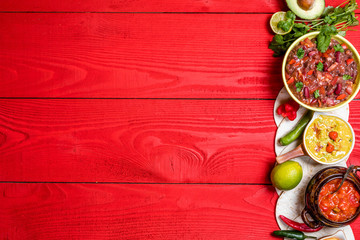 Vegetarian Mexican food concept: refried black and red beans. guacamole, salsa, chili, tortilla chips and fresh ingredients over vintage red rustic wooden background. Top view, flat lay Wall mural