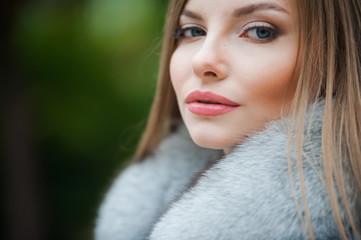 Beautiful young blonde woman wearing fur autumn coat