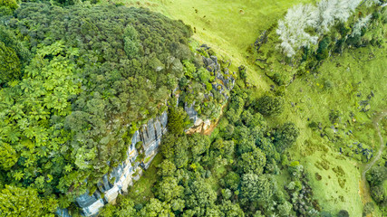 Aerial view on a rocky cliff with forest and farmland on the background. Taranaki region, New Zealand