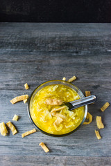egg drop soup with crispy noodles in clear bowl top view