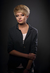Beautiful serious sexy woman with short bob blond hairstyle in suit on grey background. Closeup portrait