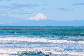 View on Mount Taranaki across Tasman sea at sunny day. Taranaki region, New Zealand.