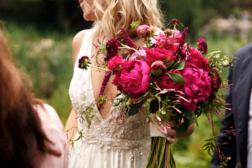 Pretty bride holds rich dark pink bouquet of peonies in her arm Fototapete