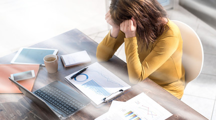 Stressed businesswoman sitting in office, light rays effect