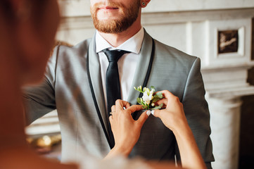 bride correcting boutonniere on grooms jacket