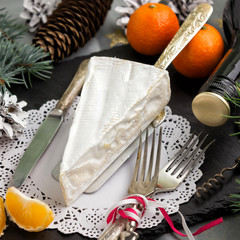 Brie cheese Cutlery fork and knife ,branches of fir, tangerines,