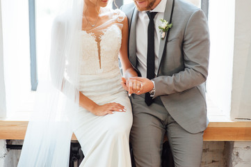 newlyweds hugging and sitting on a wooden board