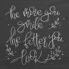The more you smile the better you look. Text on chalkboard