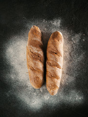 Two whole homemade buckwheat loaf bread with buckwheat flour on black textured background. Top view or flat-lay. Low key