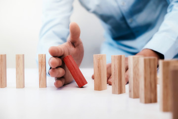 Businessman hand stop dominoes continuous toppled or risk with copyspace. Risk, Strategy, Planning management concept.