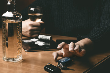 Man takes car keys after using cocaine drug and drinking whiskey. Drugs and alcohol concept