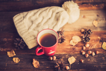 Mug of hot coffee in a woman's hand in a sweater in the autumn setting on a wooden table with a knitted scarf, sweater. Comfort, warmth, cozy