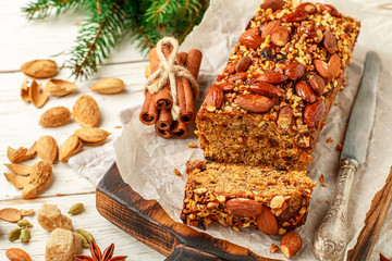 Festive Homemade Holiday Fruitcake with Nuts, Fruit and spices. Almonds, cinnamon, star anise, cardamom on the table. Christmas. New year. Selective focus