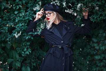 Fashion close up portrait of stylish young blond woman with red lips, trendy glasses and leather black hat in grape leaves. Autumn trendy look.  High fashion concept.