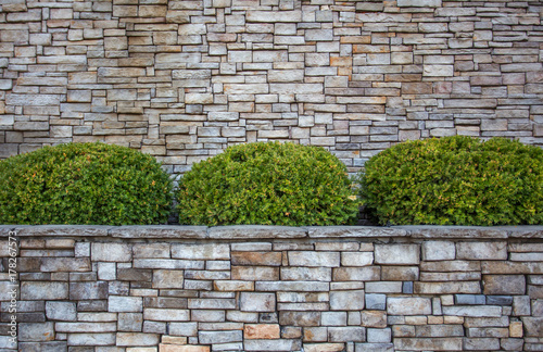 Rounded Green Shrubs In Planter Box Against A Gray And Brown Brick
