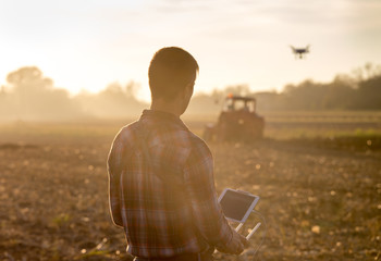 Farmer navigating drone above farmland Wall mural
