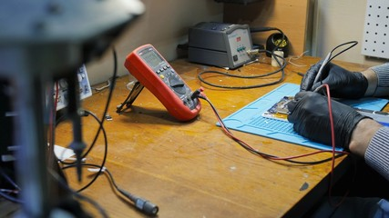 check voltage by tester. Young electrician measuring voltage in fuse board