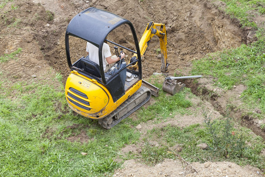 Workman using a mini digger to dig a hole for a swimming pool in a garden lawn viewed from above