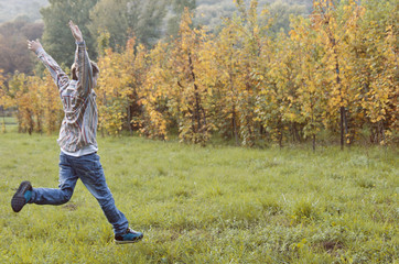 young boy jumping trough the autumn medow
