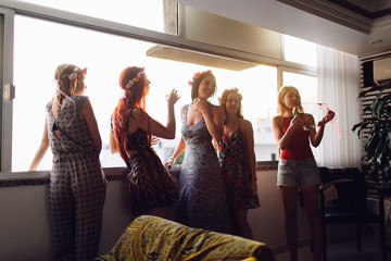 five women friends hanging out by the window