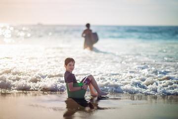 Boy sitting in a green bucket at the beach