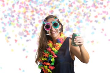 Bonita garota pulando feliz na festa de celebração bebendo cerveja com confetes caindo por toda parte sobre ela. Comemorando o ano novo, aniversario ou carnaval.