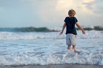 boy gets splashed in the ocean