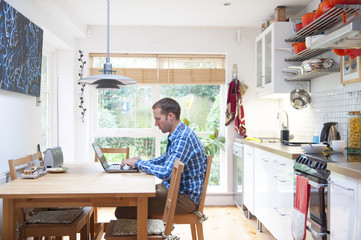 man working at a laptop in the kitchen