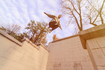A young guy performs a jump through the space between the concrete parapets. The athlete practices parkour, training in street conditions. The concept of sports subcultures among youth