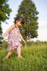 Little girl walking on the grassland