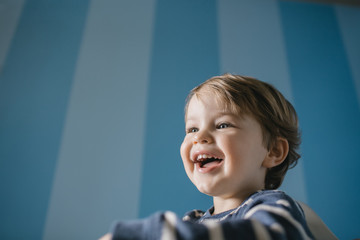 Excited smiling boy in a room with blue stripes