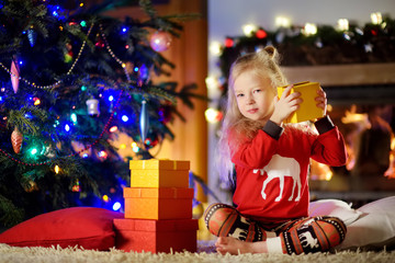 Happy little girl wearing Christmas pajamas playing by a fireplace in a cozy dark living room on Christmas eve