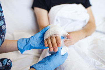 the nurse puts a bandage on a hand to a sick patient at home