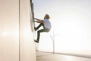 Man climbing a wall to get higher up