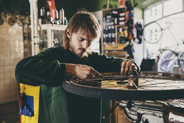 Young bicycle mechanic fixing wheel