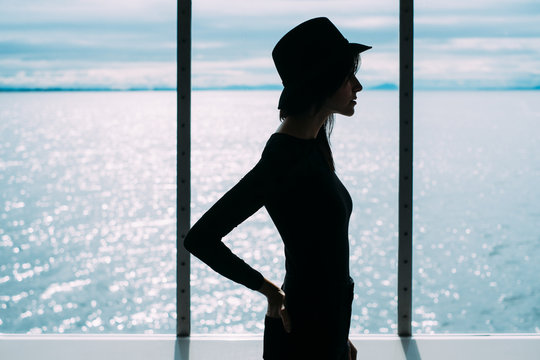 Silhouette of a woman standing in front of a window facing the ocean