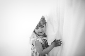 A little girl in between the sheets on a clothing line.