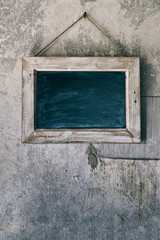 Blackboard Hanging on an Old, Rustic Concrete Wall