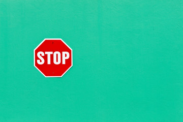 Image of a bright red stop sign against a vibrant green wall