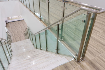 Stores à enrouleur Escalier Modern white marble stairs with steel and glass railing in a new modern building.