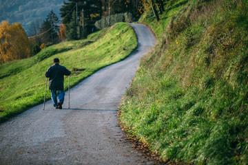 An elderly man walking outdoors