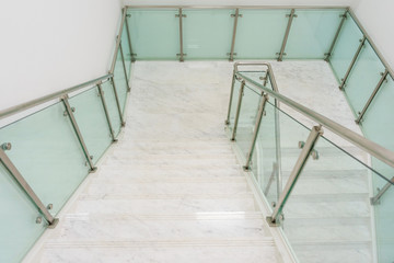 Modern white marble stairs with steel and glass railing in a new modern building.