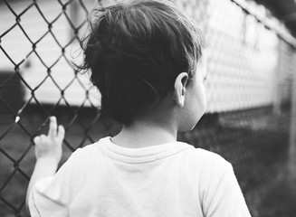boy leans against fence