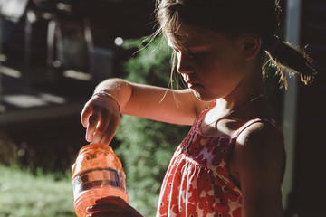 A little girl blows bubbles on a summer day.