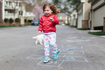 Cute toddler doing hopscotch outside