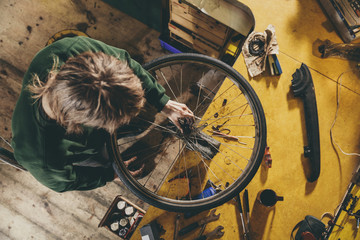 High angle shot of mechanic working on bicycle wheel