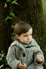 Little girl with coat and tree background
