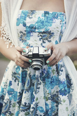 Girl holding an old retro camera in her hands